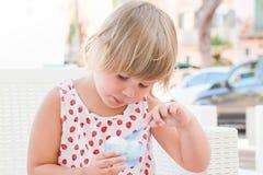 Den gulliga blonda caucasianen behandla som ett barn flickan äter den djupfrysta yoghurten Royaltyfria Bilder
