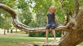 Den gulliga blonda flickan som barfota sitter på trädfilial i, parkerar under sommardag lager videofilmer
