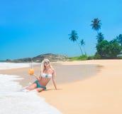 Den gulliga blonda kvinnan på havstranden mot vaggar och palmträd Royaltyfri Bild