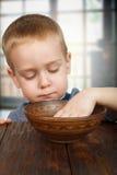 Den gulliga blonda pojken äter med händer arkivfoto
