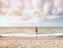 Den gulliga blonda blonda pojken som går på stranden in i det skummande havet, vinkar Blåsig sommardag, Royaltyfri Bild