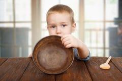 Den gulliga blonda pojken visar den tomma plattan fotografering för bildbyråer