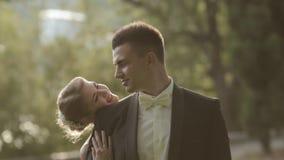 Den gulliga bruden kommer att ansa, kramar honom och kysser stock video