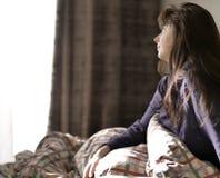 Den gulliga brunetten sitter i s?ng, n?r den har vaknat upp, ser ut f?nstret royaltyfri foto