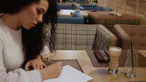 Den gulliga brunettflickan med lockigt hår skriver en dikt i en restaurang lager videofilmer
