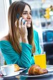 Den gulliga brunettkvinnan i kafé talar vid mobiltelefonen Fotografering för Bildbyråer