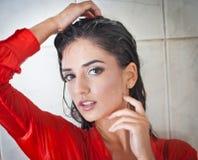 Den gulliga brunettkvinnan med den perfekta kroppen som poserar i erotiskt, poserar under dusch med vått hår och den genomskinlig arkivbild