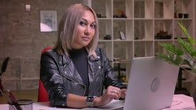 Den gulliga caucasian blonda kvinnlign sitter nära hennes bärbar dator och ser rak på kameran med nätt leende, medan skriva in lager videofilmer