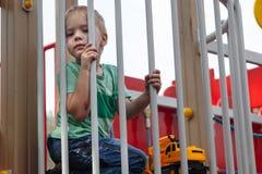 Den gulliga caucasian blondinen behandla som ett barn pojken sitter under staketet av barnlekplatsen Gulligt, allvarligt och humi arkivbild
