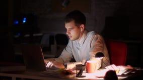 Den gulliga caucasian tillfälliga mannen är lyssnande musik i hörlurar och att flytta sig, medan sitta och skriva i bärbar dator  stock video