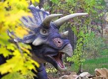 den gulliga dinosaurietriceratopsen ser ut bakifrån en buske i en grön äng royaltyfria bilder