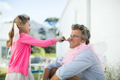 Den gulliga dottern i den felika dräkten som sätter makeup på henne fäder, vänder mot Arkivfoto