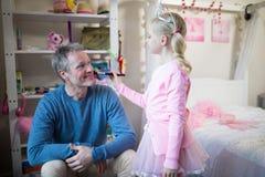 Den gulliga dottern i den felika dräkten som sätter makeup på henne fäder, vänder mot Fotografering för Bildbyråer