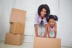 Den gulliga dottern som packar upp att flytta sig, boxas med hennes moder Arkivbild