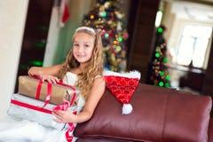 Den gulliga eleganta flickan firar jul och nytt år med gåvor Fotografering för Bildbyråer