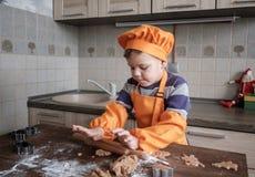 Den gulliga europeiska pojken i en dräkt av kocken gör ljust rödbrun kakor royaltyfria bilder