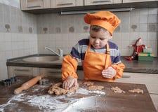 Den gulliga europeiska pojken i en dräkt av kocken gör ljust rödbrun kakor fotografering för bildbyråer