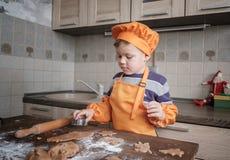 Den gulliga europeiska pojken i en dräkt av kocken gör ljust rödbrun kakor royaltyfri fotografi