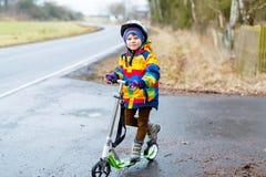 Den gulliga förskole- ungepojkeridningen på sparkcykeln parkerar in Arkivbilder