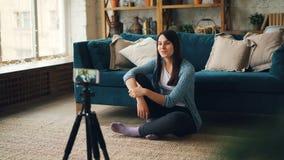 Den gulliga flickabloggeren antecknar videoen för hennes online-vlog som inomhus sitter på golv hemma som ser smartphonekameran lager videofilmer