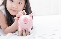 Den gulliga flickahanden satte pengar till piggybank Arkivfoton