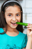 Den gulliga flickan äter en peppar Fotografering för Bildbyråer