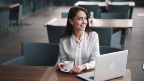 Den gulliga flickan blandar socker i kopp kaffe i kafét, bärbar dator på tabellen, ultrarapid stock video