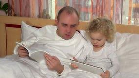 Den gulliga flickan för det lilla barnet med minnestavladatoren och blir skallig faderläseboken lager videofilmer