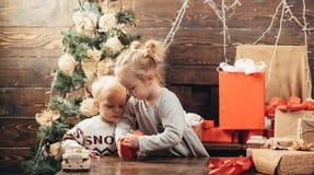 Den gulliga flickan f?r det lilla barnet dekorerar julgranen inomhus Morgonen f?r Xmas Ungen tycker om ferien arkivfoto