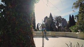Den gulliga flickan går på en antik terrass i härlig trädgård på en solig dag lager videofilmer