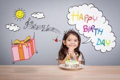 Den gulliga flickan gör en önska på födelsedag lycklig bakgrundsfödelsedag Arkivfoto