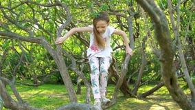 Den gulliga flickan i blommande trädgård för äppleträd tycker om den varma dagen lager videofilmer
