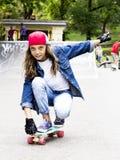 Den gulliga flickan i en baseballmössa med en skateboard i en skridsko parkerar sportar royaltyfri foto