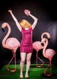 Den gulliga flickan i fuchsiapaljetter klär att vila och att dansa med tre stora flamingo på svart bakgrund arkivfoton