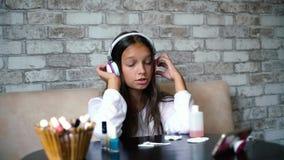 Den gulliga flickan i hörlurar och hem beklär lyssnande musik på telefonen och att sjunga, medan göra manikyr lager videofilmer