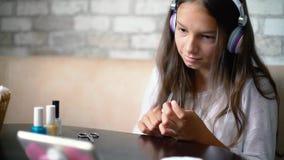 Den gulliga flickan i hörlurar som pratar online-danandemanikyrpolering, spikar med fri och kopieringsutrymme arkivfilmer