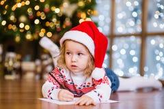 Den gulliga flickan i röd julhatt skrivar brevet till Santa Claus Arkivbild