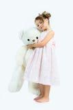 Den gulliga flickan i rosa färger klär den stora vita björnen för kramar på ljus bakgrund Arkivbilder