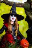 Den gulliga flickan klädde till allhelgonaaftondräkten i mörk skog Royaltyfri Foto