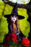 Den gulliga flickan klädde till allhelgonaaftondräkten i mörk skog Royaltyfri Bild