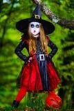 Den gulliga flickan klädde till allhelgonaaftondräkten i mörk skog Fotografering för Bildbyråer