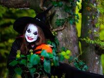 Den gulliga flickan klädde till allhelgonaaftondräkten i mörk skog Arkivfoton
