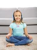 Den gulliga flickan lyssnar musik Arkivbilder