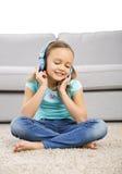 Den gulliga flickan lyssnar musik Royaltyfri Bild