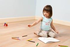 den gulliga flickan målar pennan arkivfoto