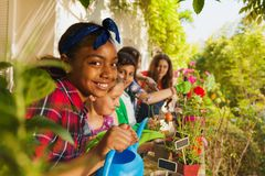 Den gulliga flickan med att bevattna kan arbeta i trädgård royaltyfria bilder