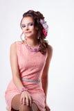 Den gulliga flickan med blommor i hennes hår i en rosa klänning ler Arkivfoto