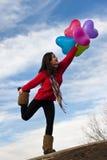 Den gulliga flickan med en grupp av hjärtaballonger på blått skidar ballonger Royaltyfri Bild