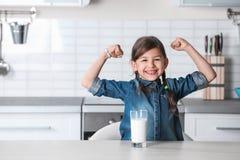 Den gulliga flickan med exponeringsglas av mjölkar på tabellen i kök royaltyfri bild