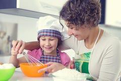 Den gulliga flickan med hennes moder bakar kakor hemma arkivbild